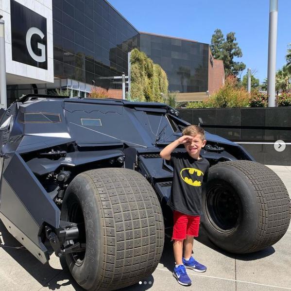 a boy in front of Batman's Tumbler