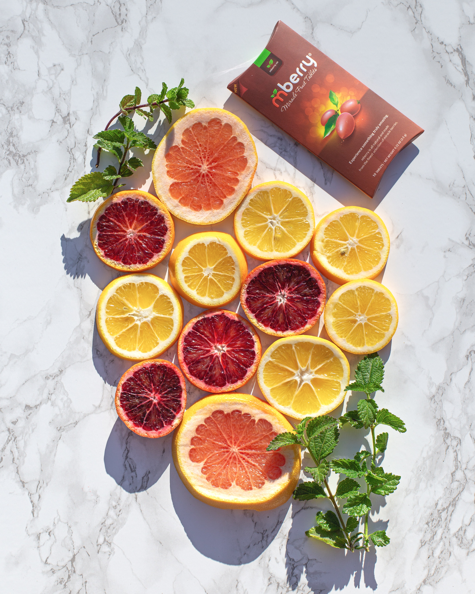 Arrangement of sliced blood oranges, pomelo, and lemons with a sprigs of mint. Featuring mberry tablets.