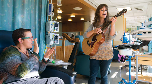 Photo of a graduate student, Betsy Hartman signing to a patient going through chemotherapy.