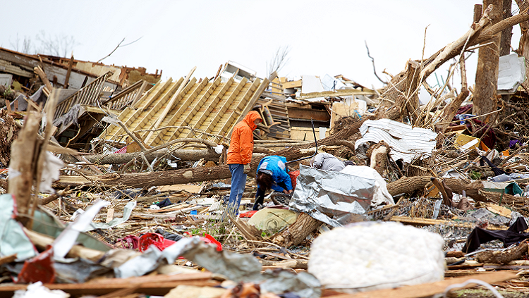 Two people stand in the debris from a hurricane. Trees are broken in half, personal belongings are scattered, and remnants of houses are shown.