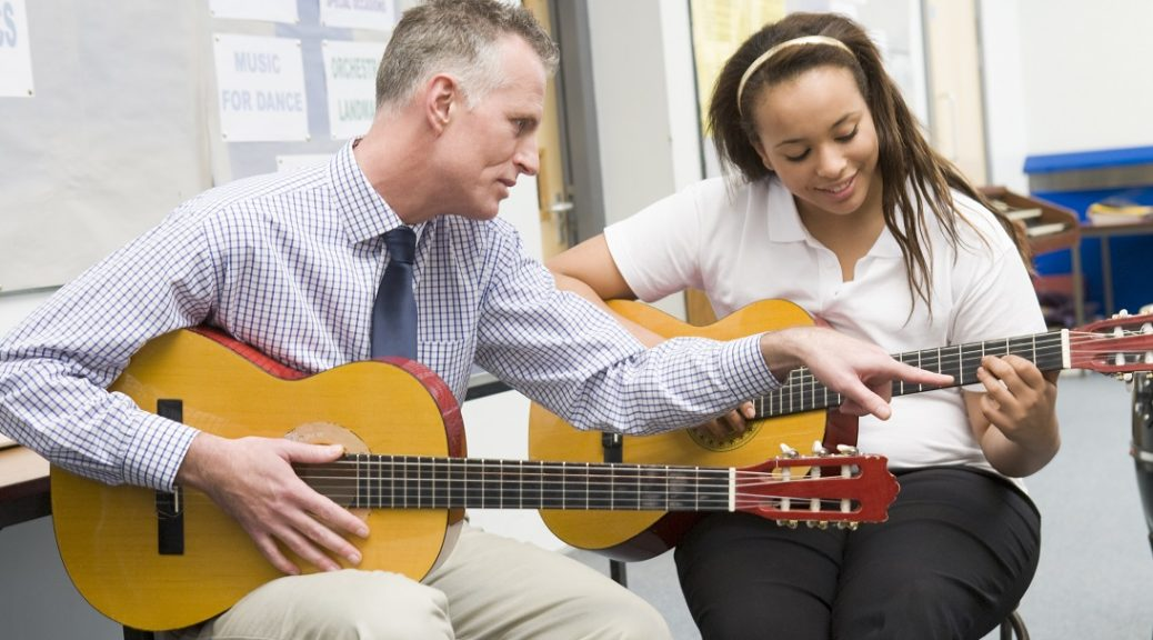 A man teaching a woman how to play guitar. Each person is holding a guitar while the man points out what string to play on the girl's guitar.