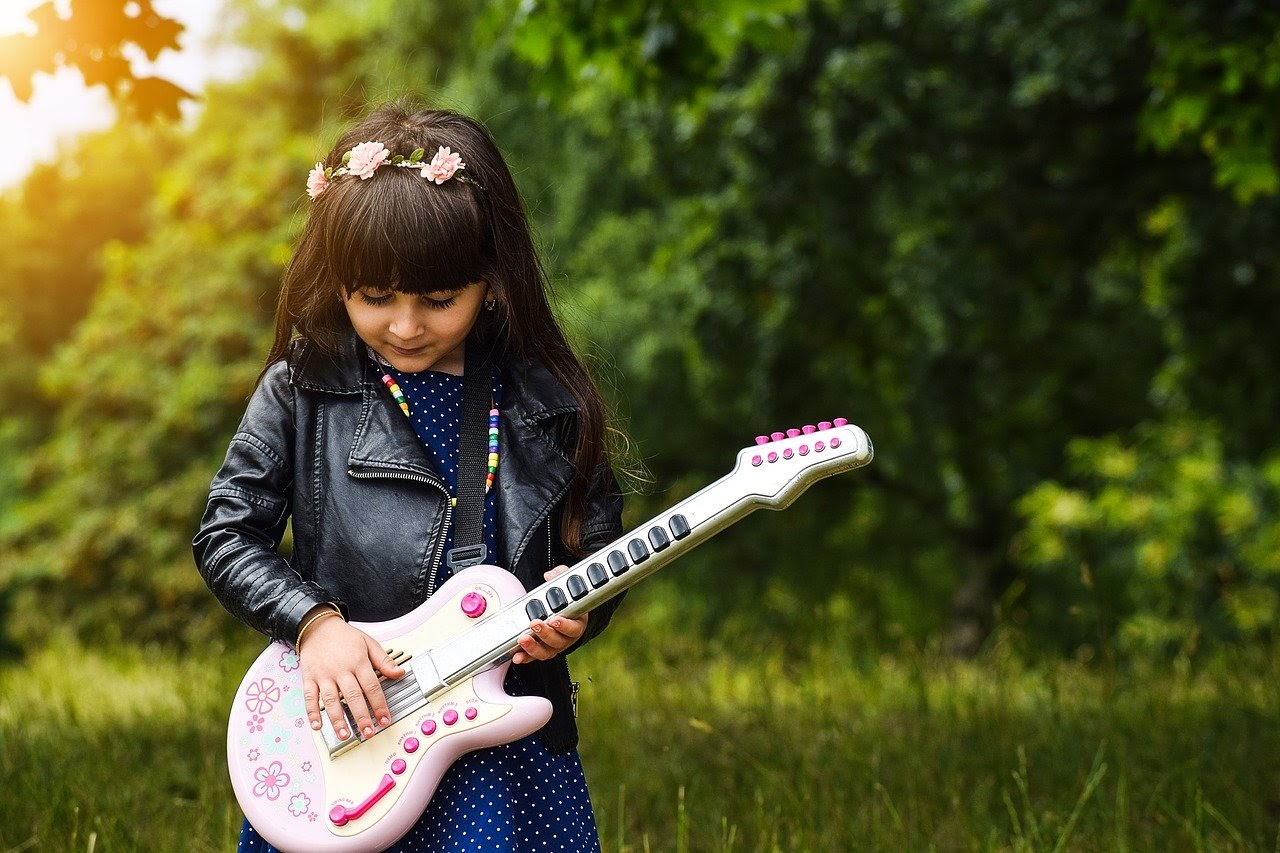 A little girl wearing a leather jacket plays a pink toy guitar.
