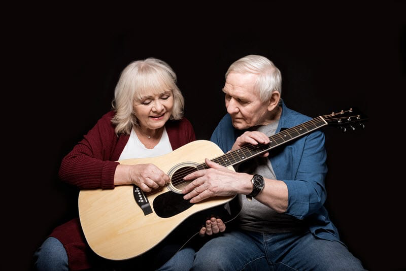 older man and woman sharing a guitar. woman is making chords and the man is strumming.