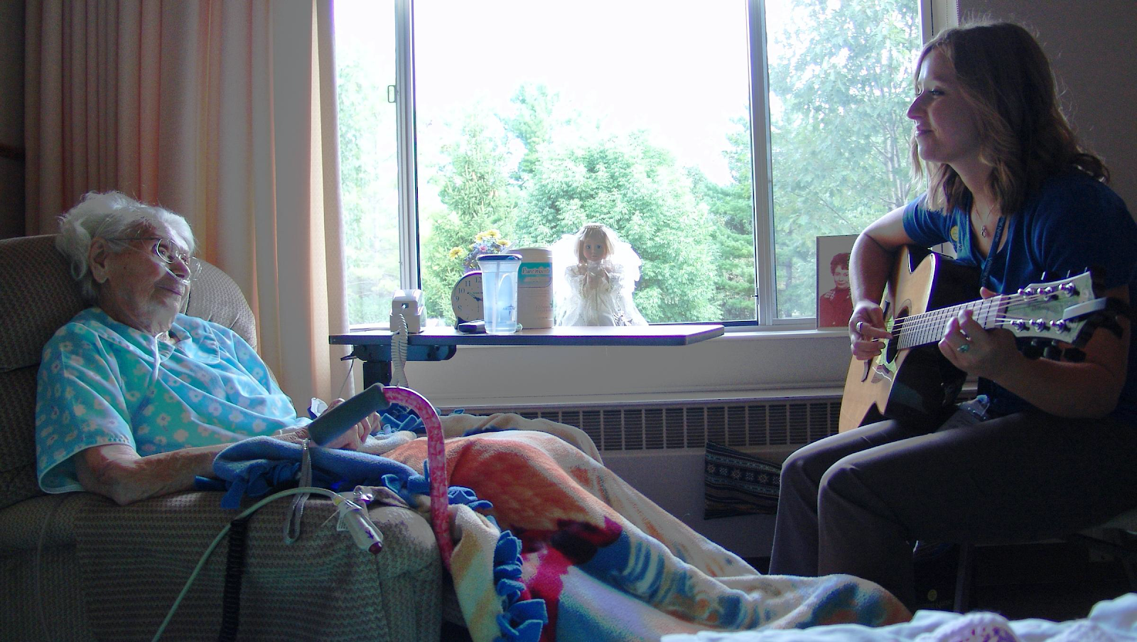 woman sitting in a recliner in a hospital with a music therapist nearby. She is holding a guitar.