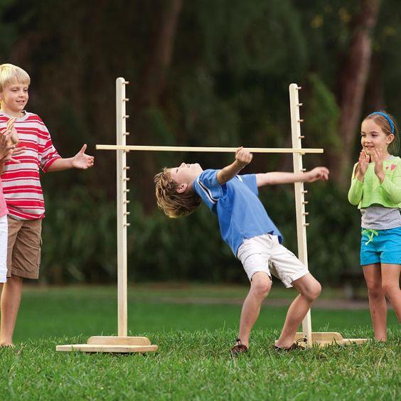 little kids playing limbo outside.