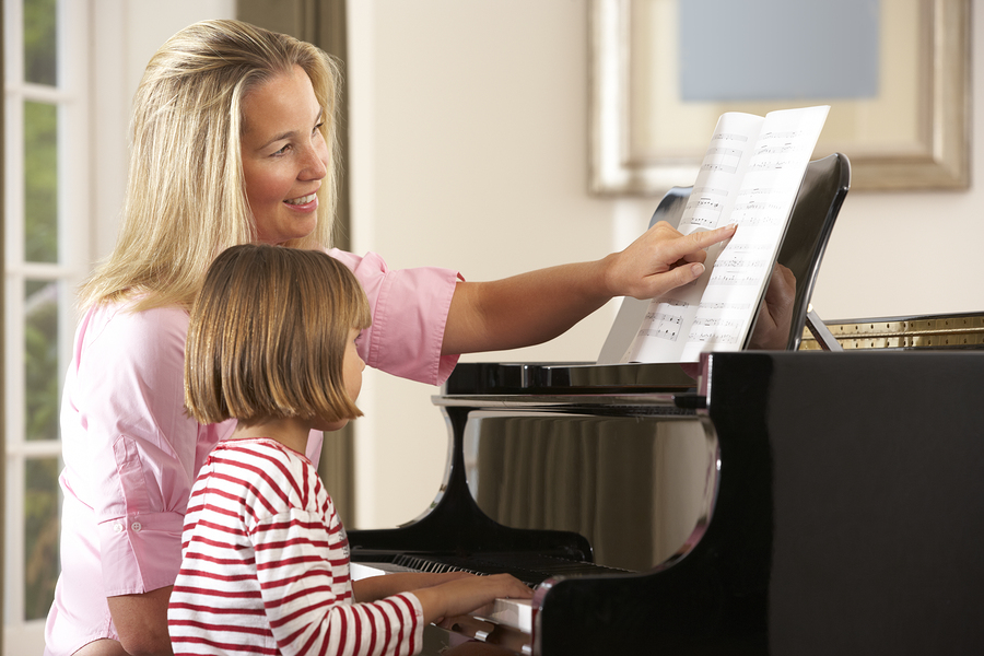 little girl playing people. blonde middle aged woman pointing to sheet music