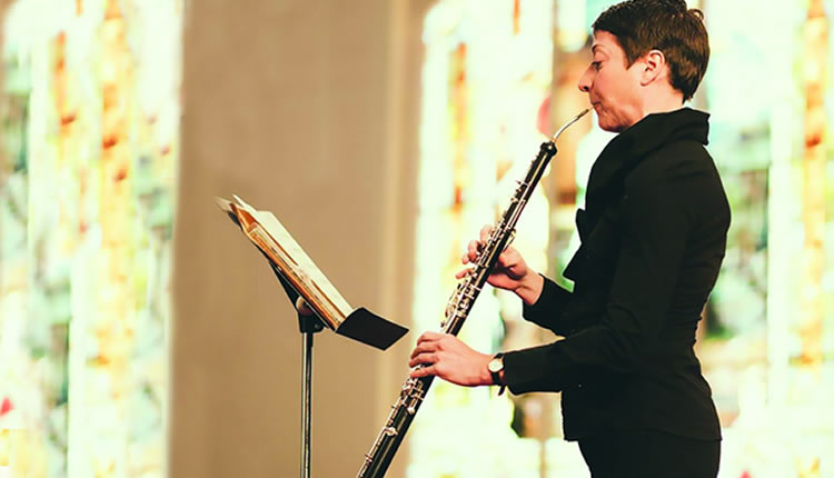 A woman in a black formal outfit plays the oboe in concert.