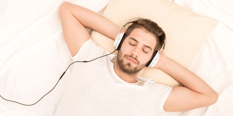 A man in a white shirt falls asleep with headphones on.