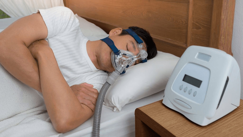 A man sleeps on a white bed while wearing a CPAP machine mask.