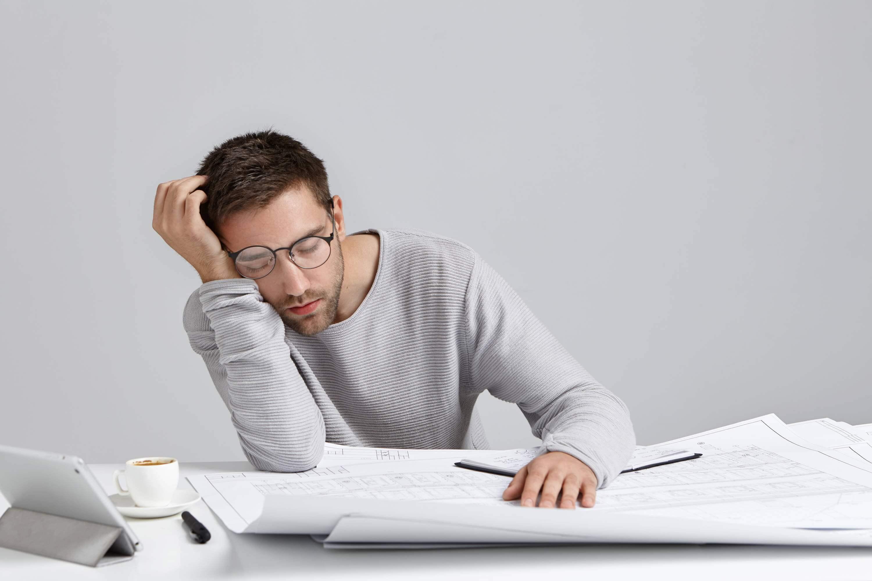 A man wearing glasses and a gray shirt falls asleep at his desk..