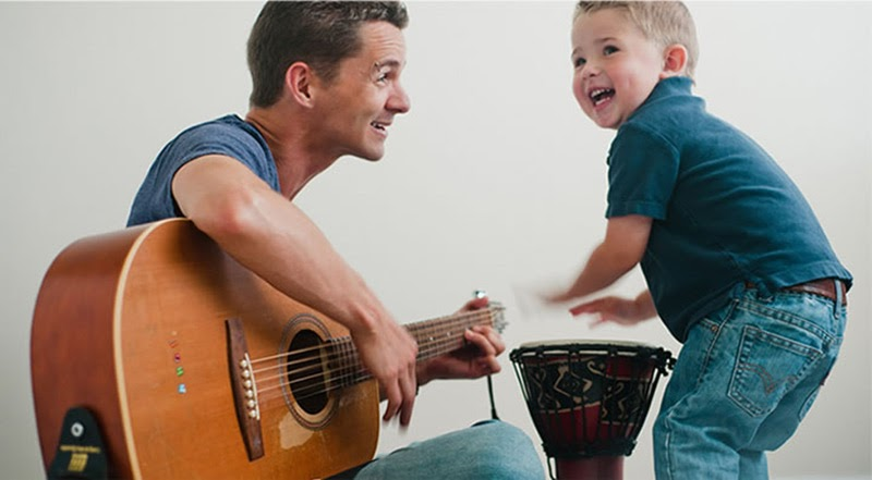 A man plays guitar with a small boy in a blue shirt playing a drum.