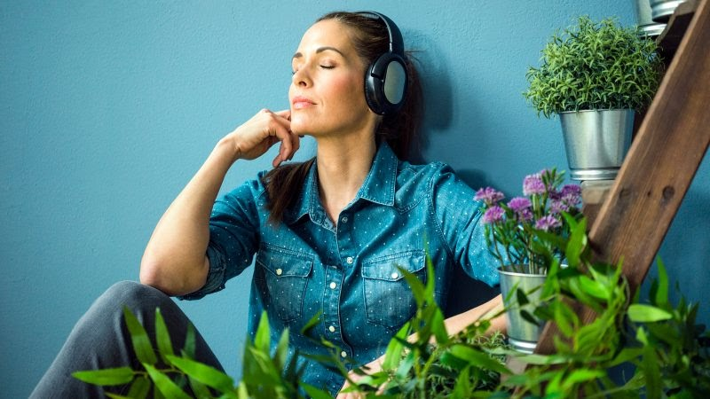 A woman in a blue blouse listens to music in a room filled with plants.