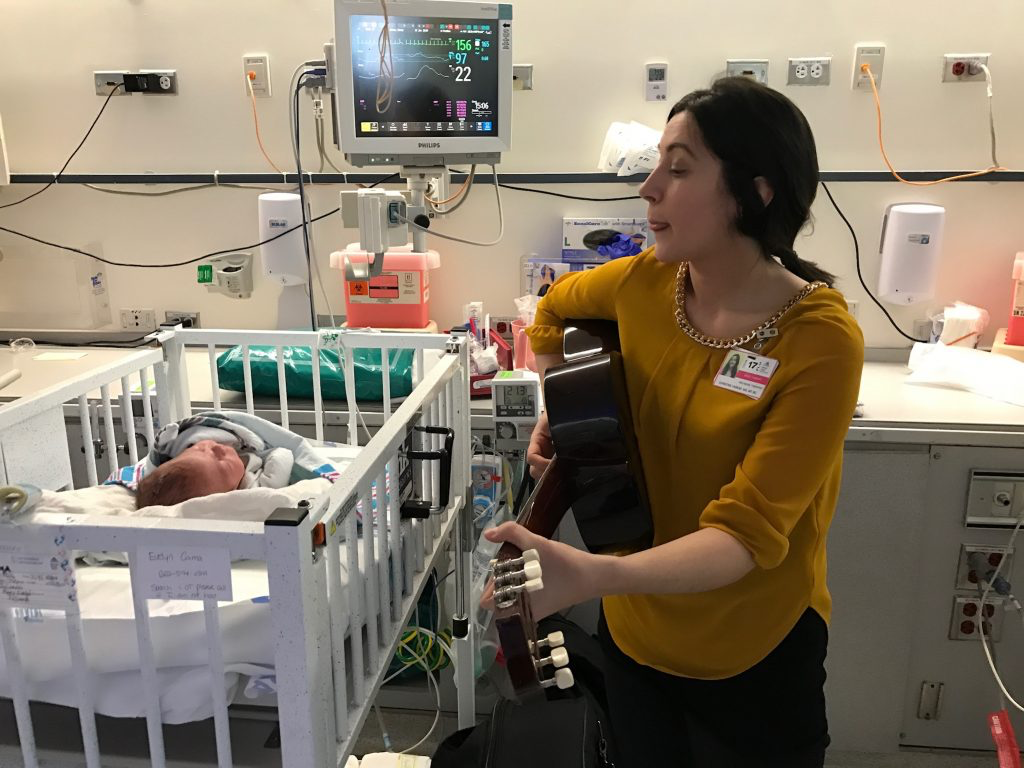 music therapist playing guitar and signing to a baby in the NICU