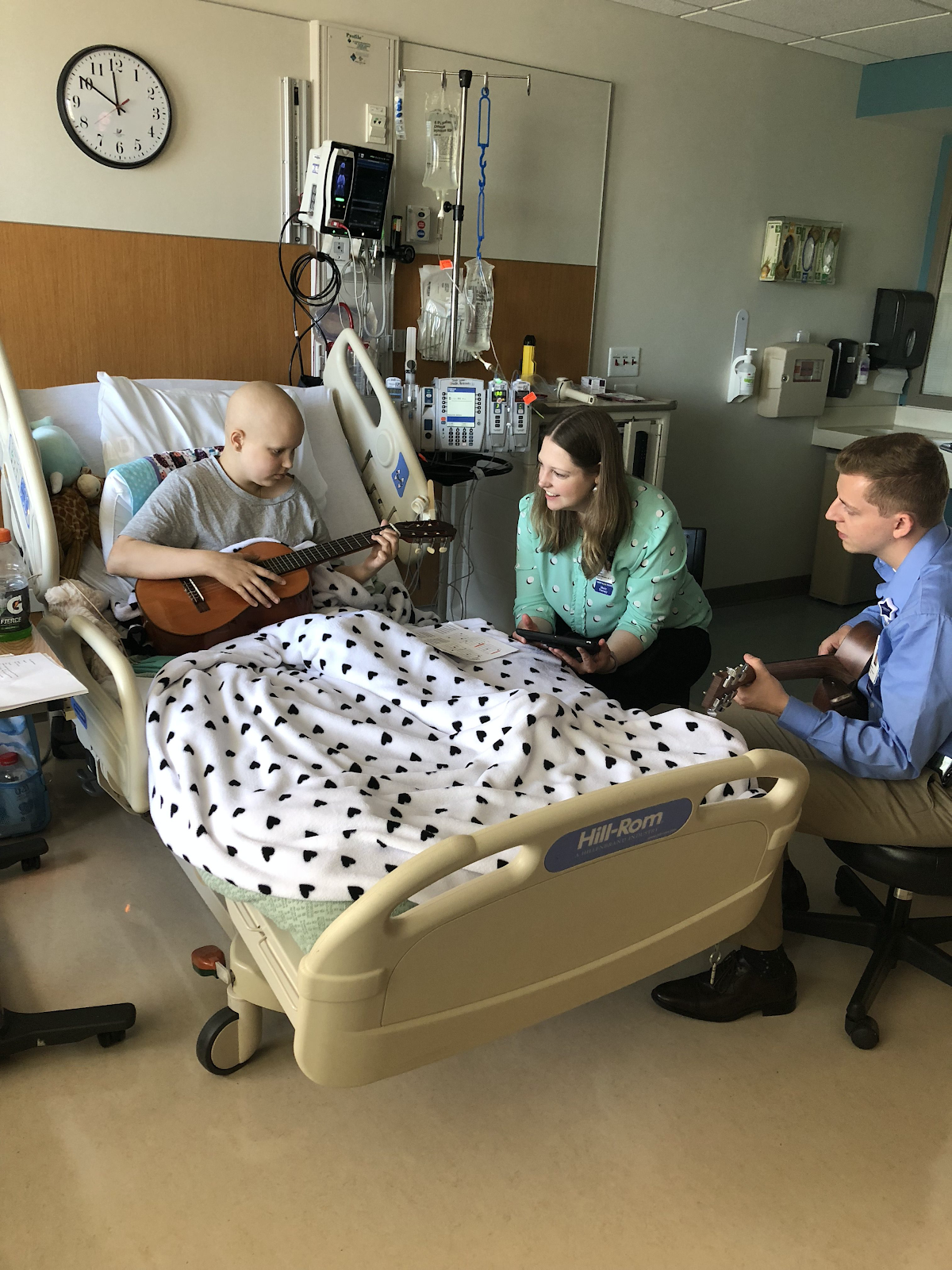 child in hospital bed playing guitar. woman sitting bedside and music therapy sitting at the bottom of the bed playing guitar too.