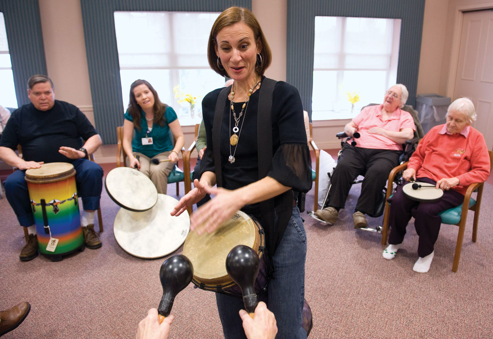 woman (music therapist) playing drums in a circle of older people playing other instruments like drums and shakers
