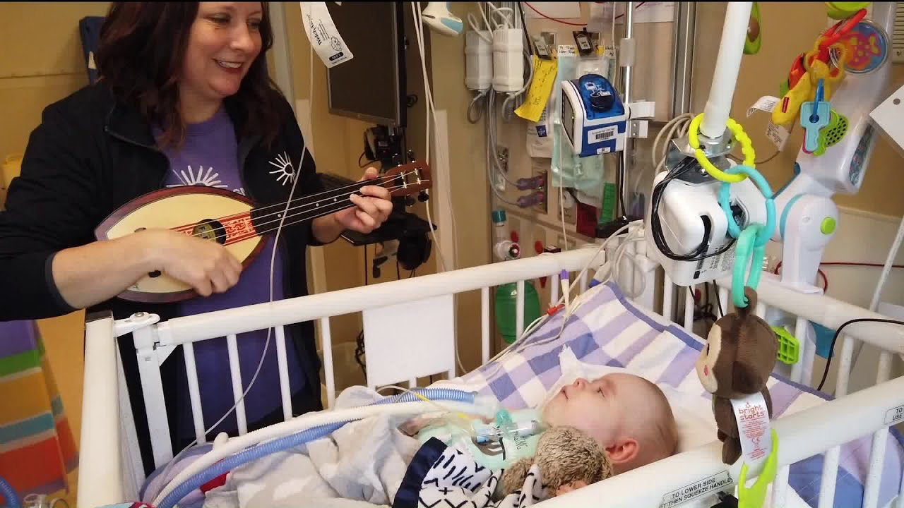 music therapist singing to baby in hospital crib