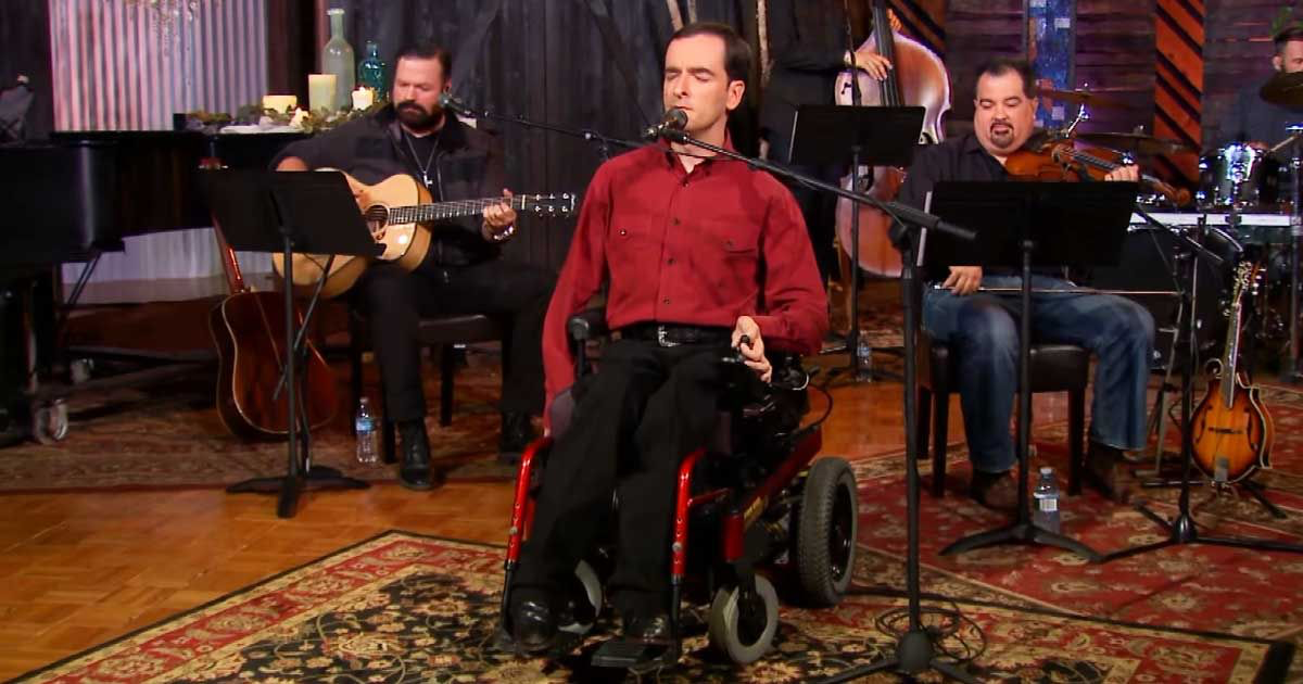 man in wheelchair singing on stage with live band