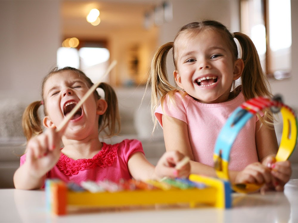 Two little girls in pink shirts play the xylophone passionately.