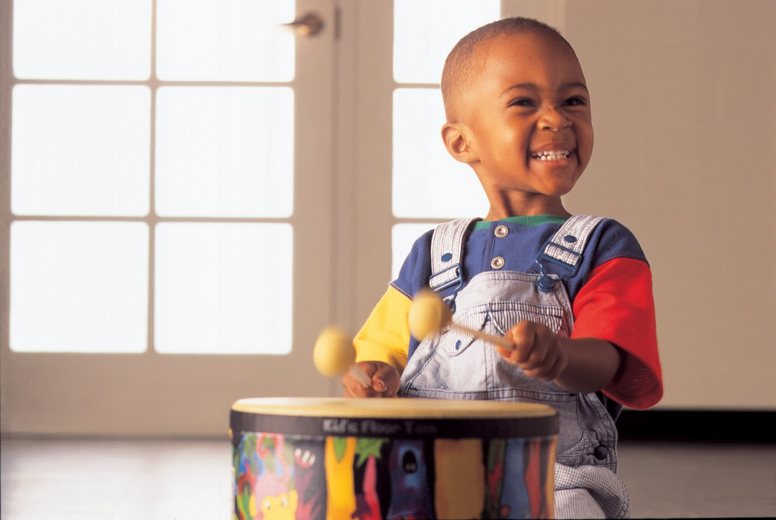 A little boy in overalls plays a drum excitedly.