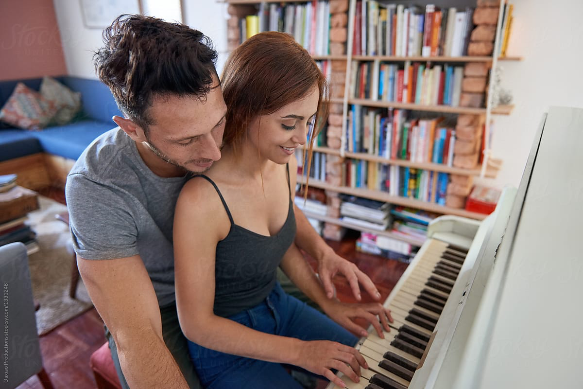 girl playing piano while sitting on man's lap.