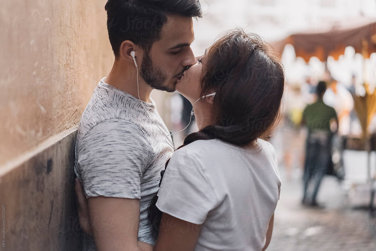 woman and man kissing with headphones in