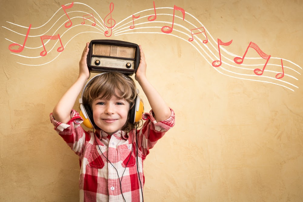 A young boy in a plaid shirt holds a stereo with red music notes above his head.