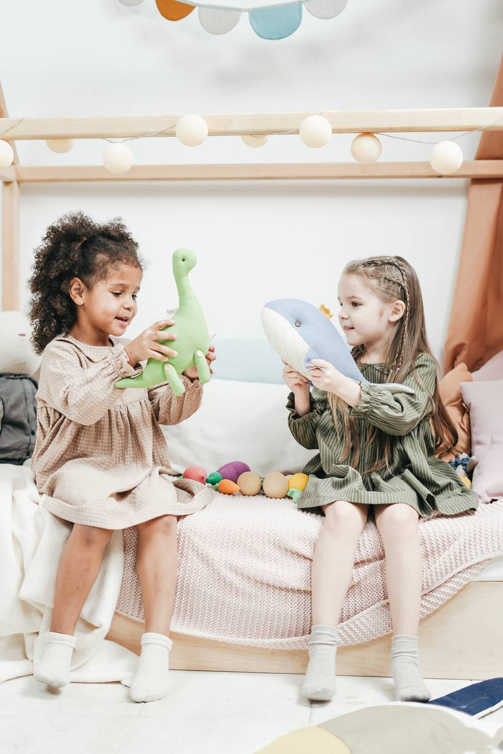 two little girls playing with stuffed animals. one is holding a dinosaur the other is holding a whale.