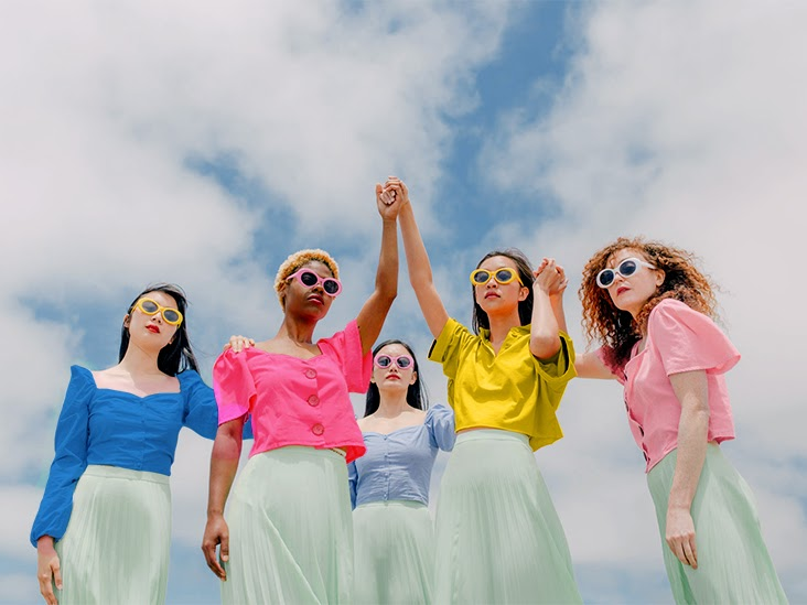 Women wearing brightly colored shirts stand together supporting each other.