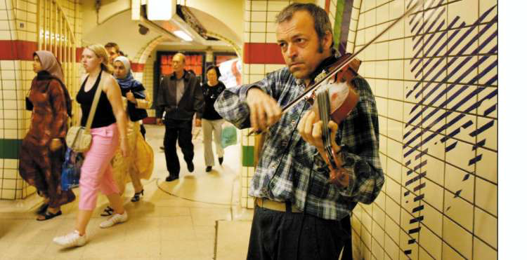 A violinist wearing a flannel shirt plays in an underground subway.