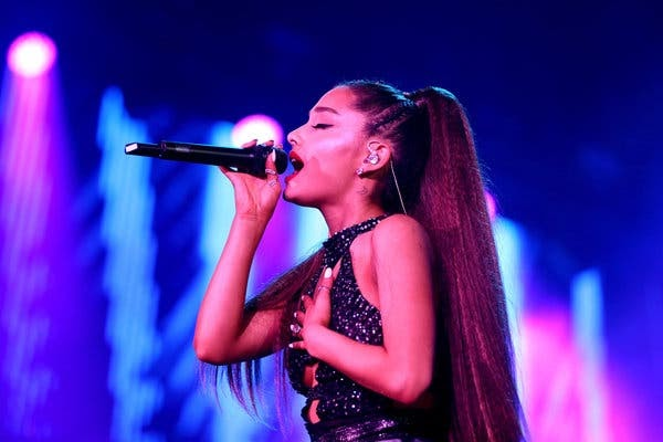 Ariana Grande sings a pop song on a stage lit with blue and purple.