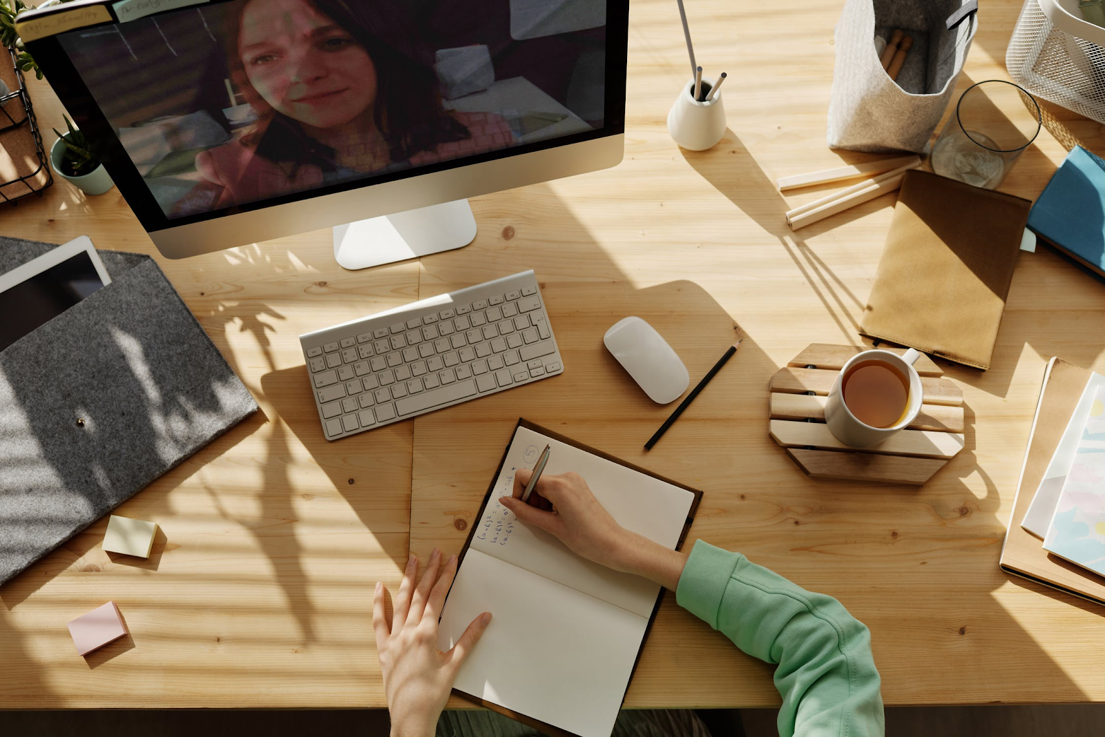 individual on video chat while writing in notebook