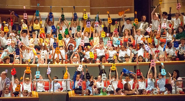 Many children in an auditorium holding up their colorful Ukelele's overhead.