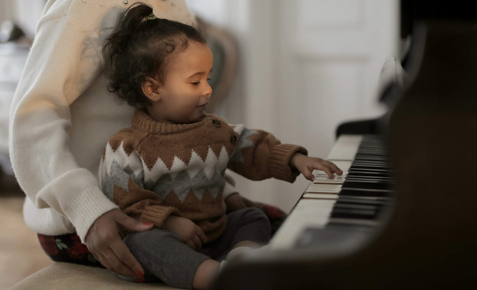 Child sitting at a piano with their hand on the keys while a parent sits behind them.