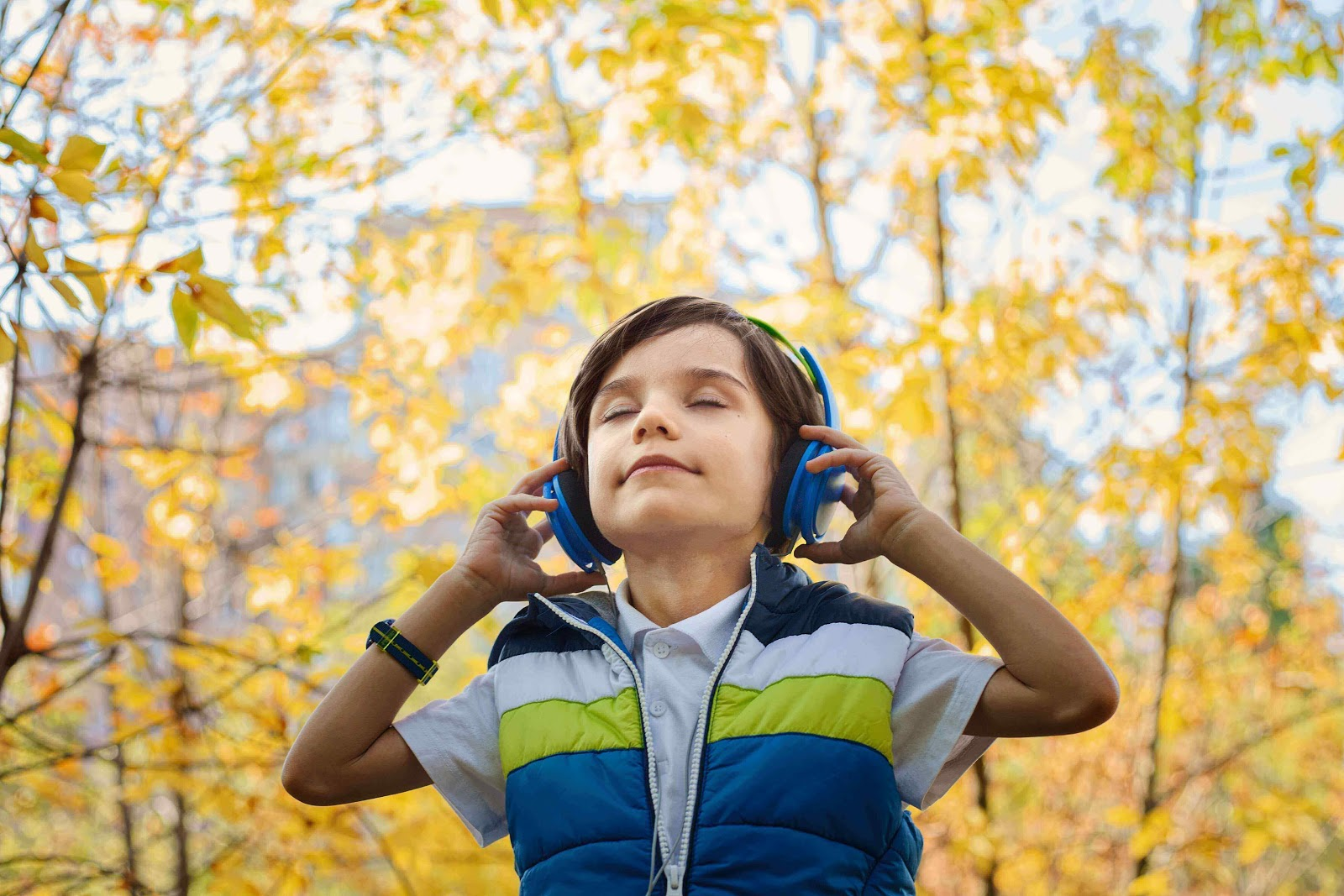 Child with headphones on holding them over his ears with a peaceful look on his face.