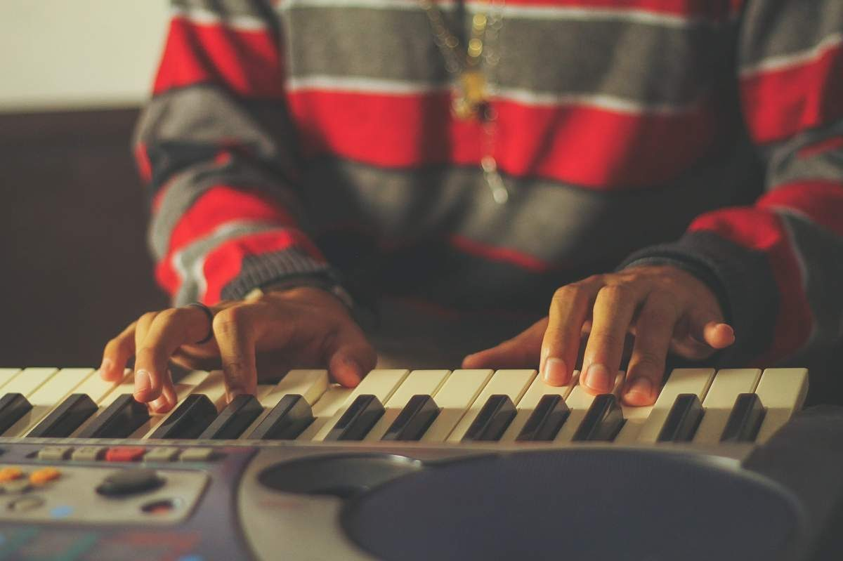 The hands of someone in a gray and red striped sweater playing a keyboard.