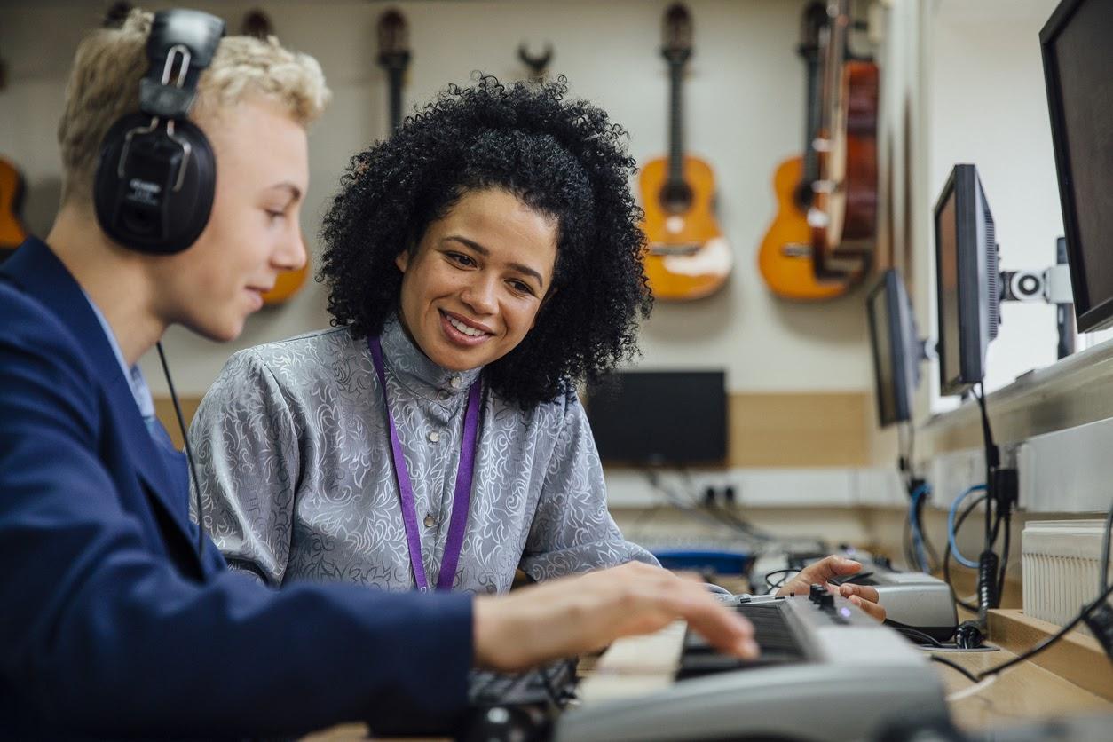 Teacher instructing student on music technology