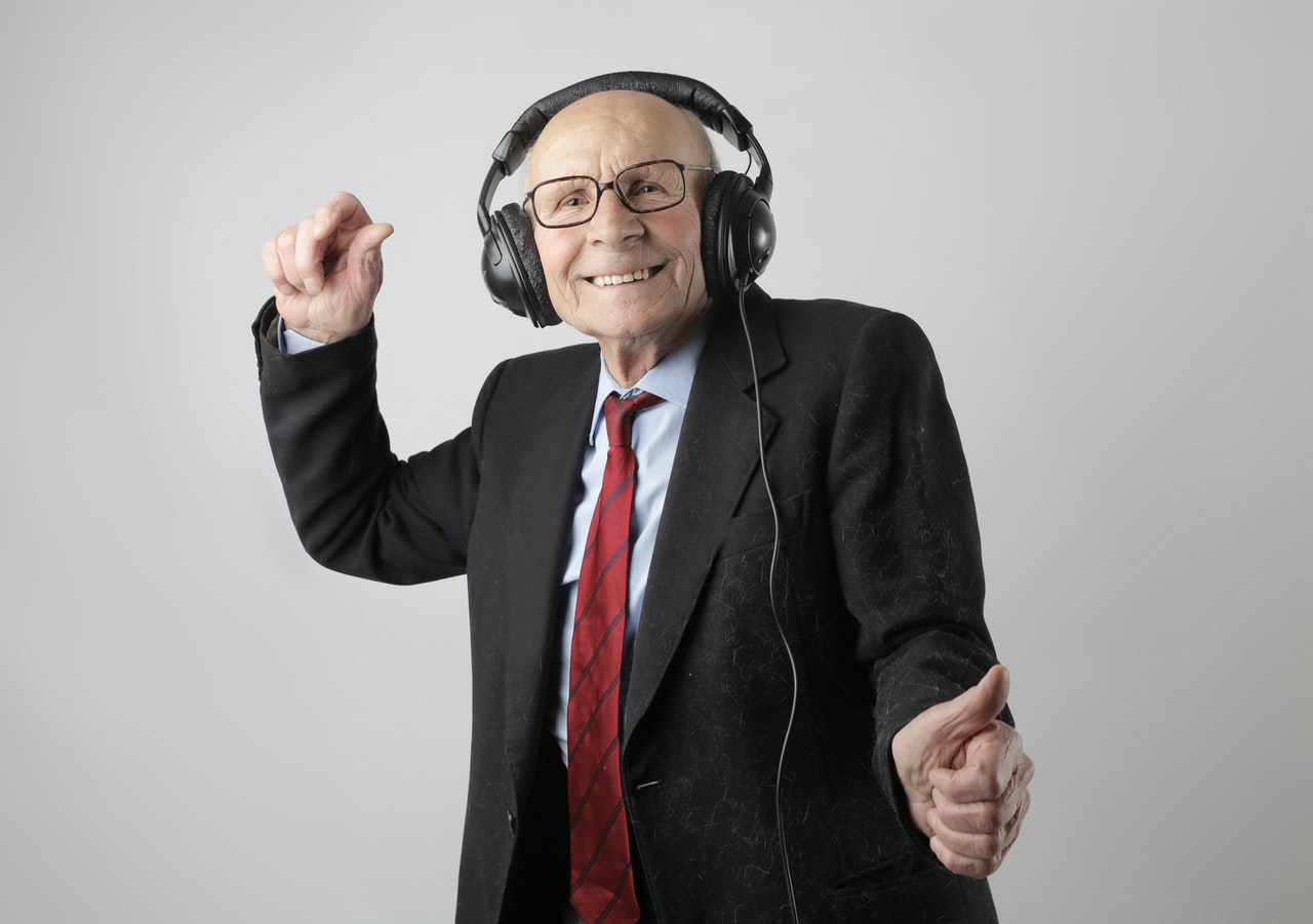 Older man in a black suit and glasses smiles while dancing and listening to music with headphones.