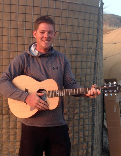 Young man named Jake Keller smiles while playing a guitar outside his military tent.