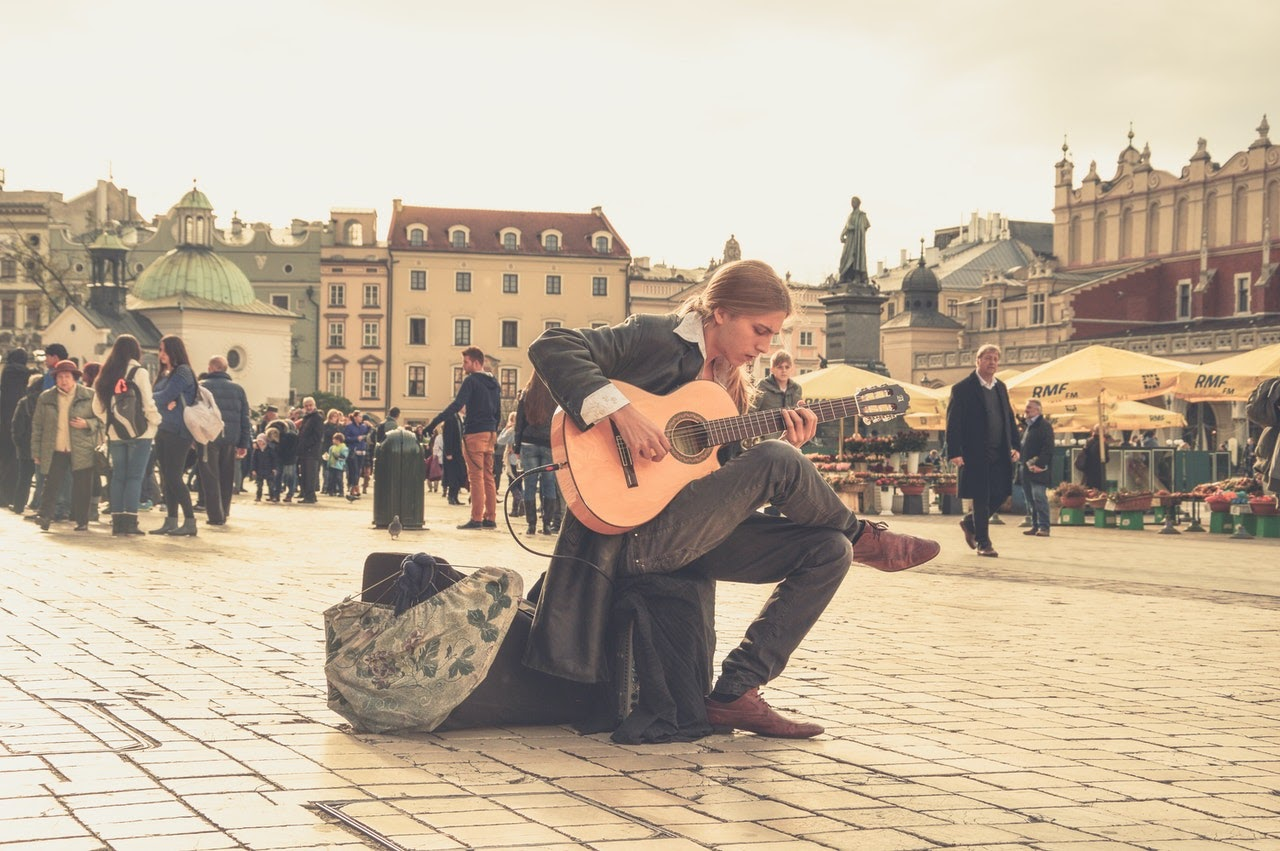 Person plays a guitar while sitting within a busy and crowded plaza area. Crowds of people stand around talking and listening to the live music.
