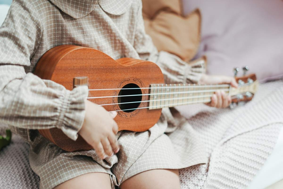 Childs hands playing the ukulele