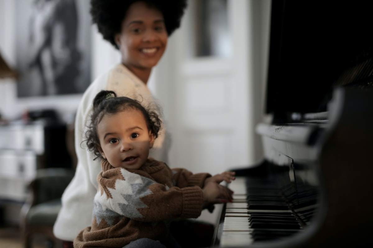 A child and adult sitting at a piano smiling while the child plays the piano