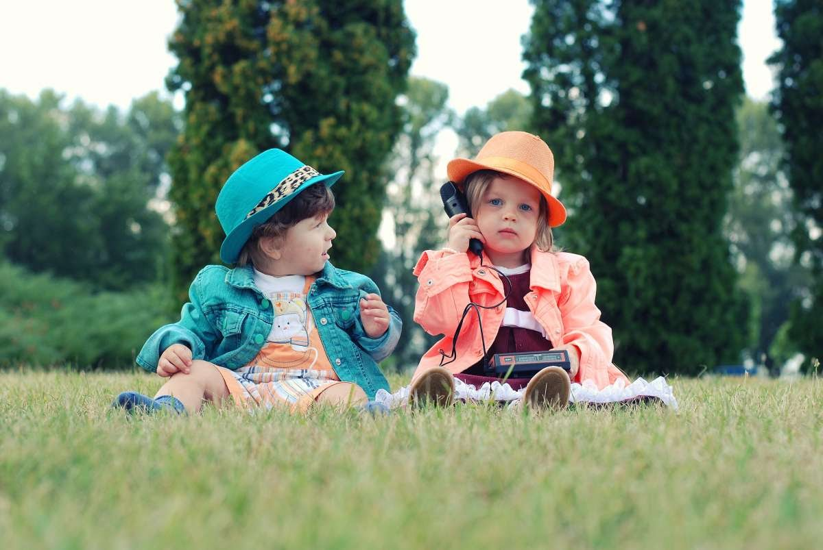 Two children sitting in some grass wearing brightly colored clothes, one is holding up a microphone.