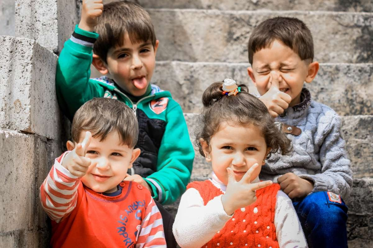 Four kids sitting on steps making silly faces and holding up thumbs up signs