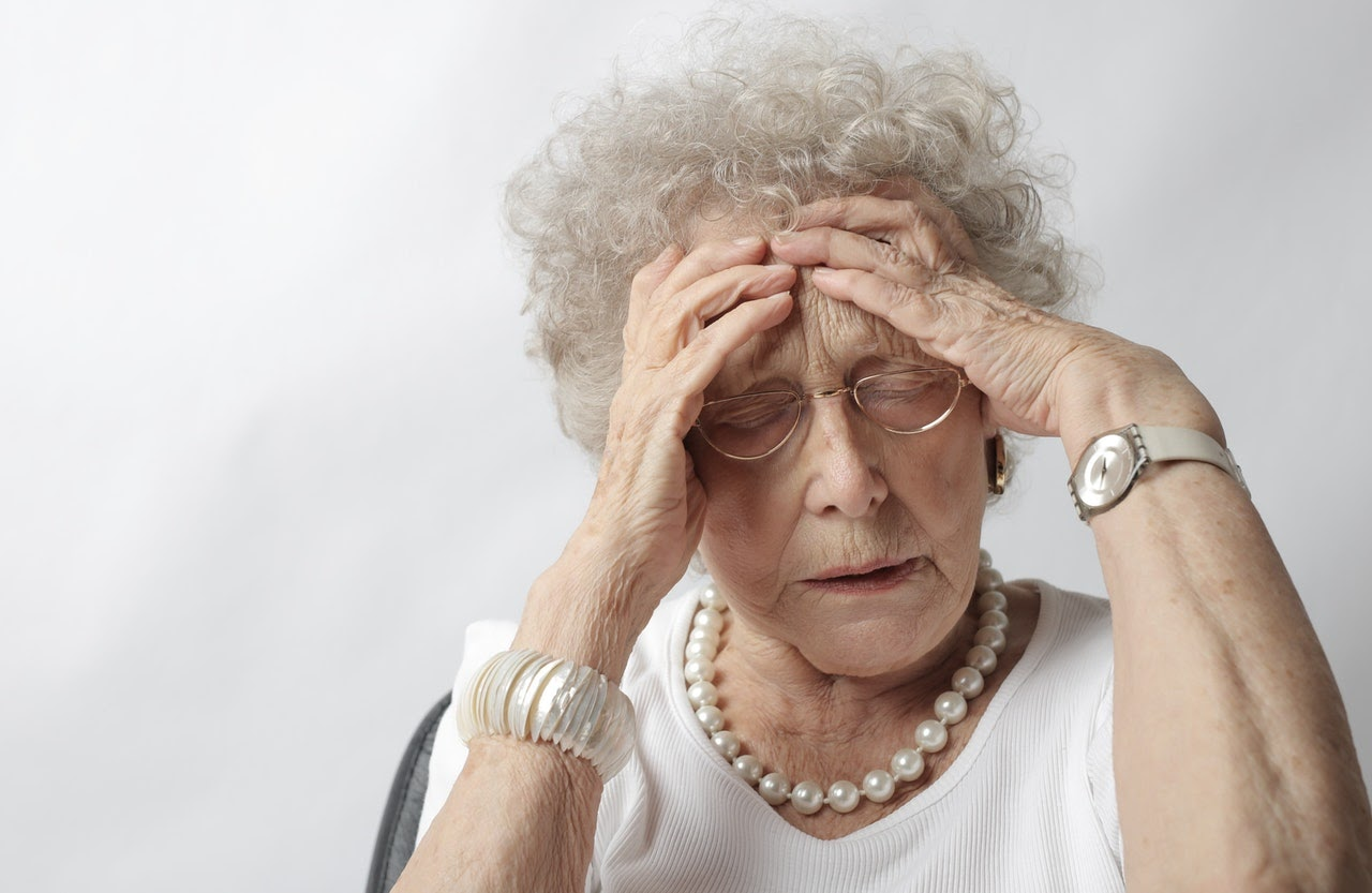 Elderly woman holding head with a look of discomfort on her face. She has a stress headache.