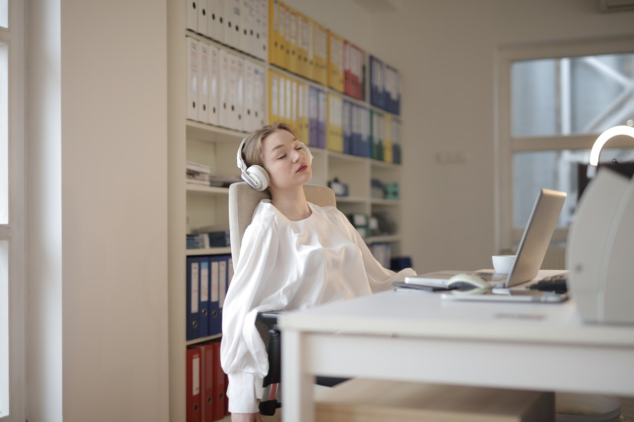 Woman reclines at her desk and has a look of contentment on her face as she listens to music through headphones.