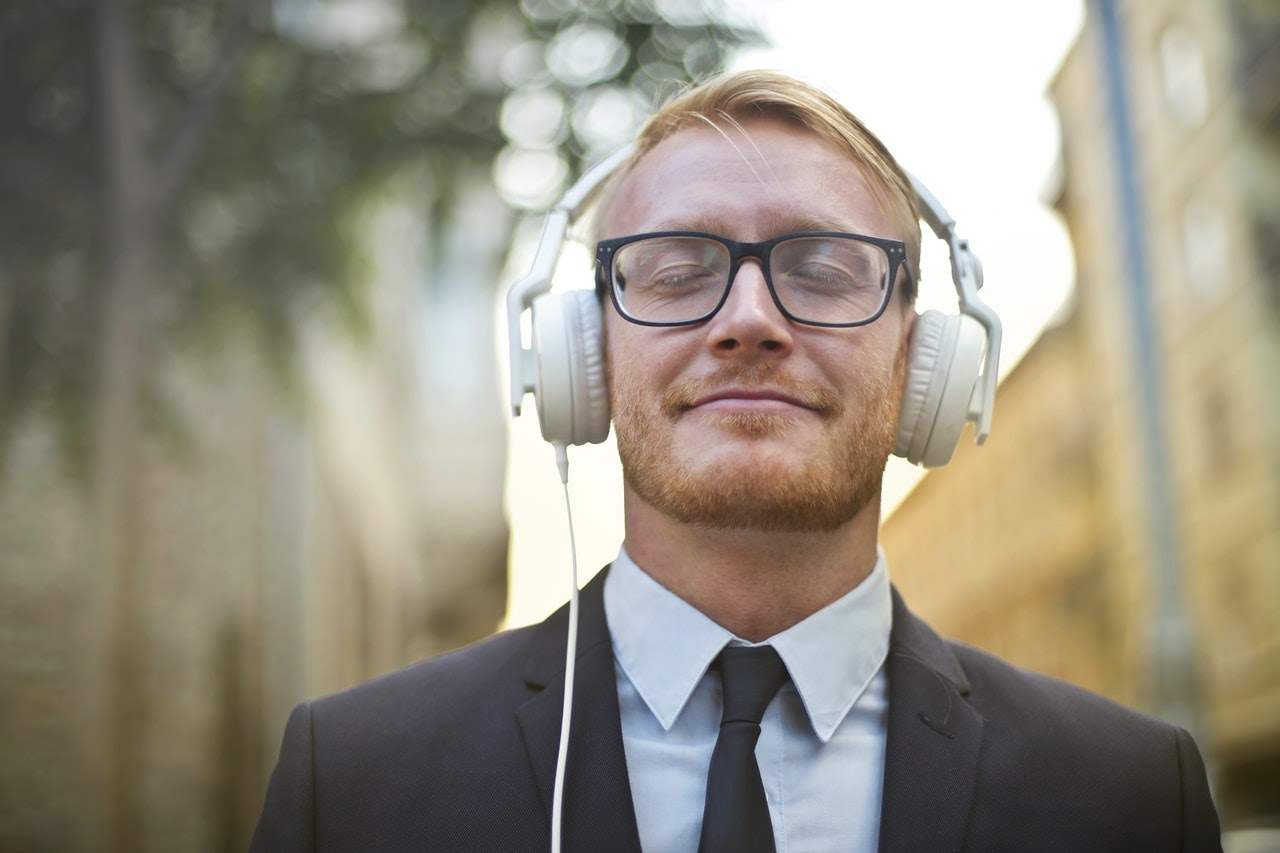 Adult man smiling contently as he listens to music through a pair of white headphones. He wears a suit and is walking through a neighborhood.