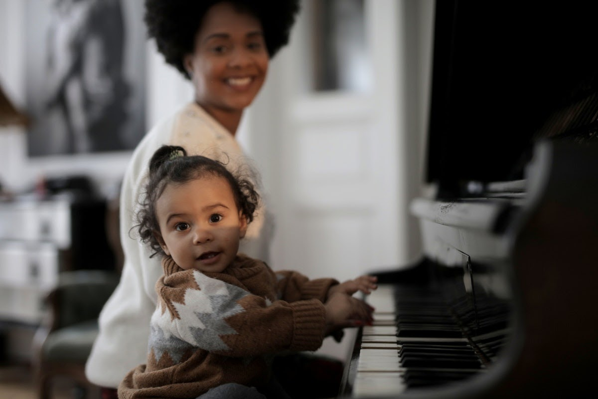 mother teaching daughter piano to reach milestones