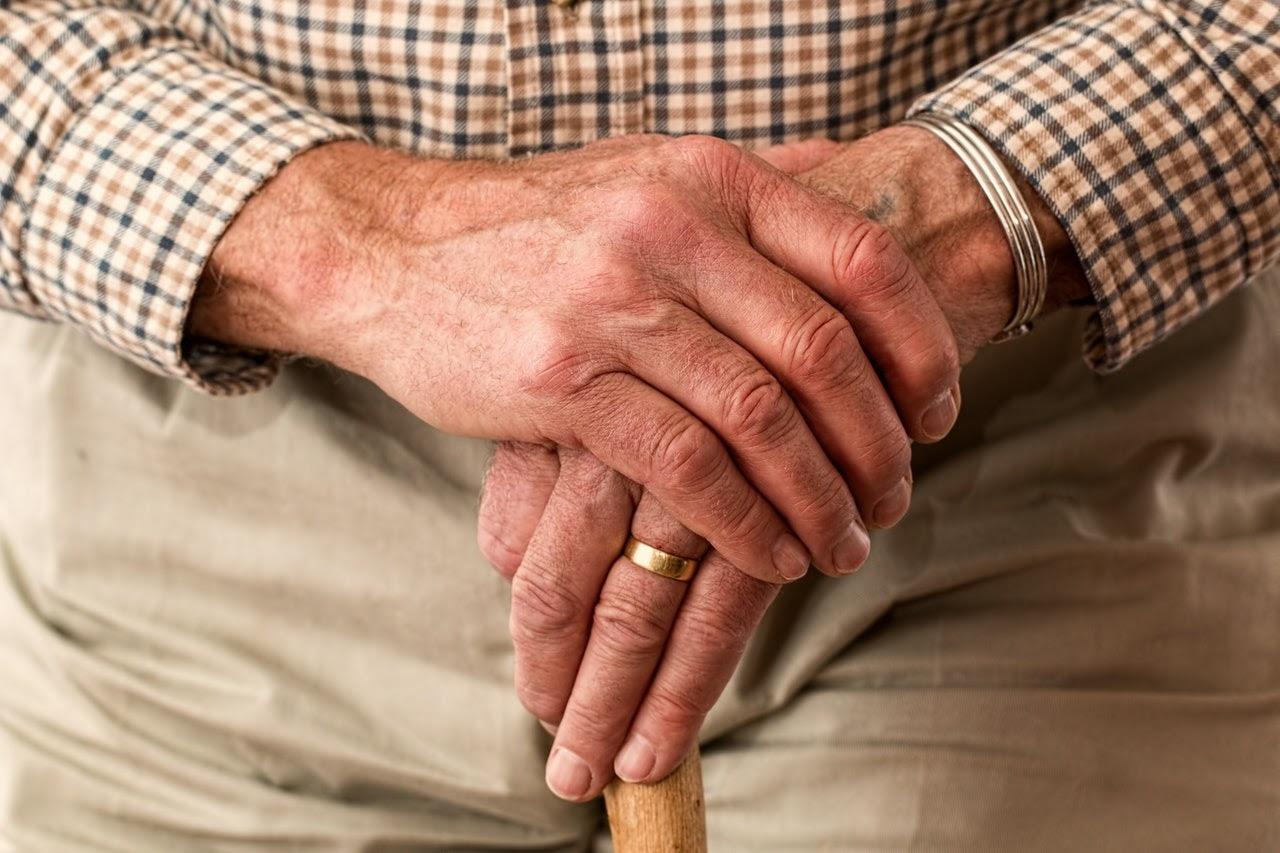 Older person holding hands together