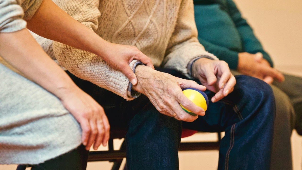Older person holding tennis ball for physical therapy