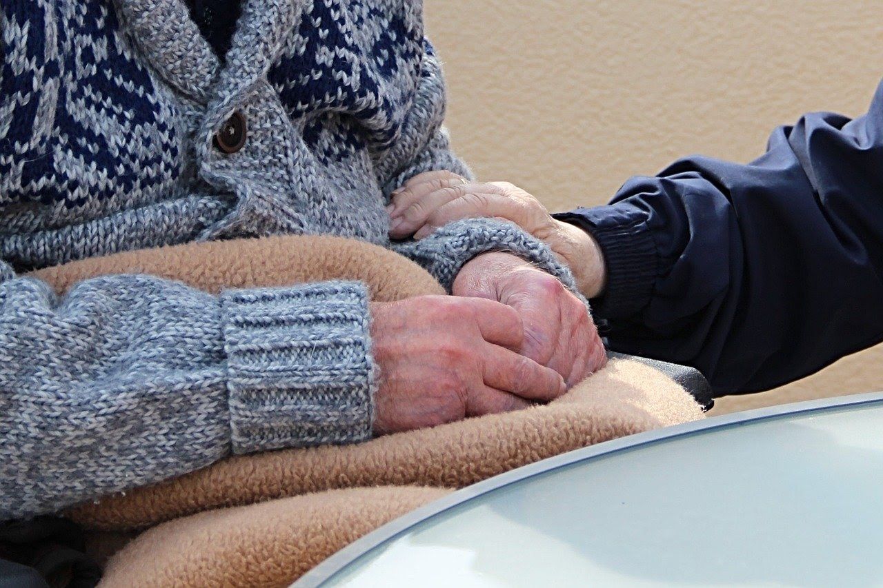 Older person's arm being held by another person's arm